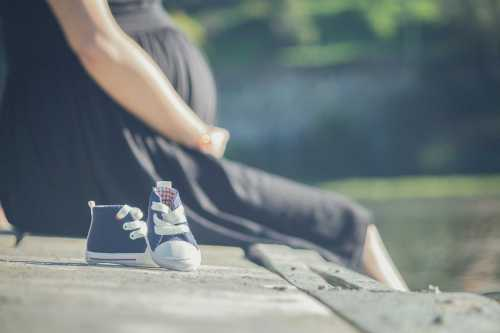 pregnant woman sitting next to a pair of tiny shoes
