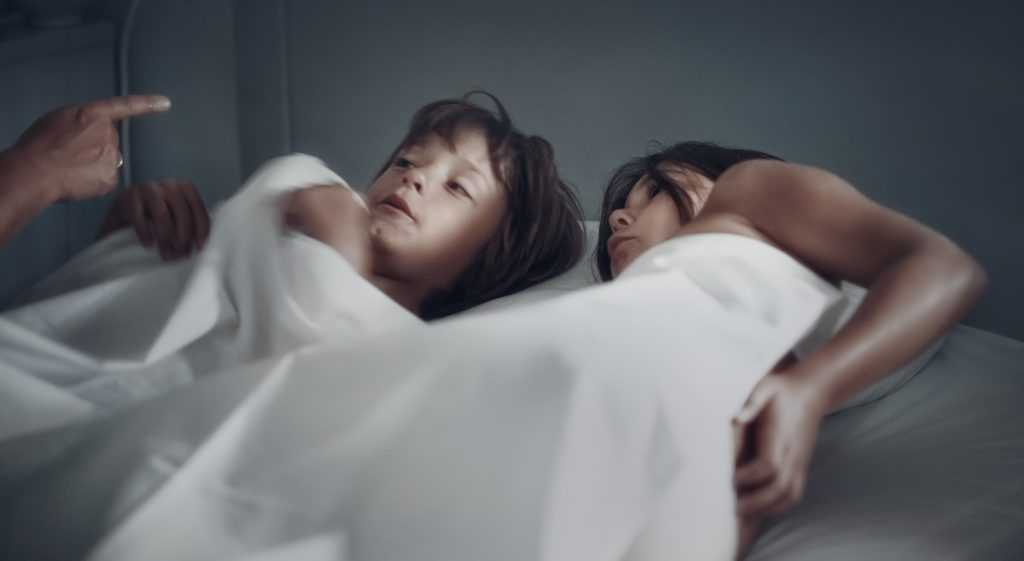 young child lying in bed with mother