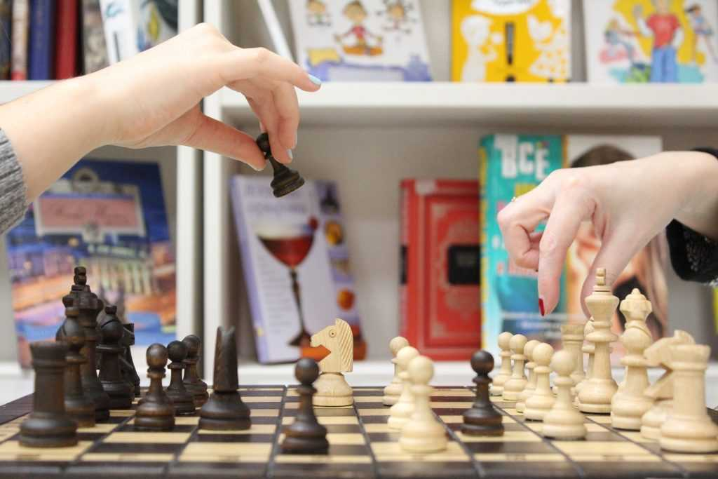 chess board, with hands moving chess pieces in front of a bookcase filled with children's books