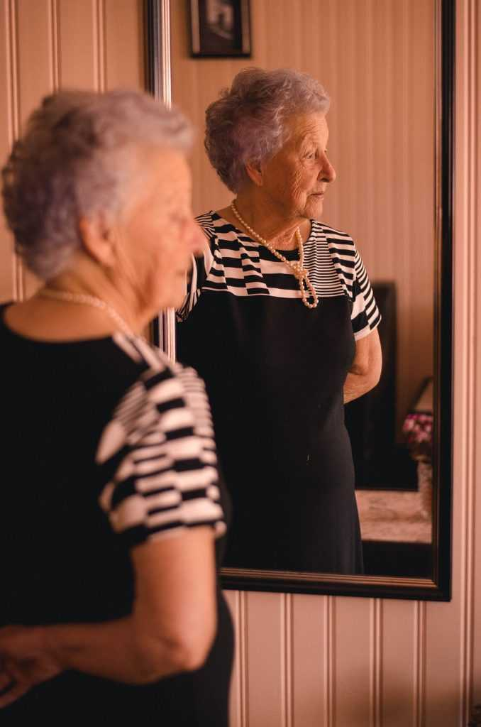 elderly woman looking into a mirror