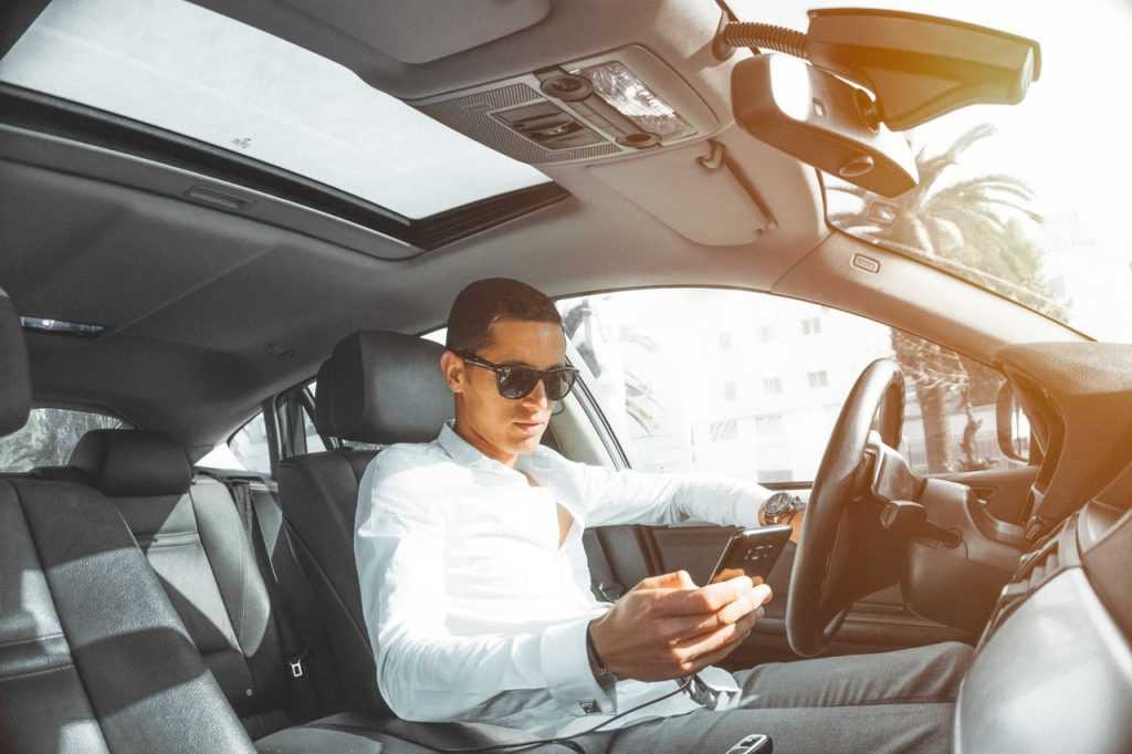 man sitting in his car looking at a phone
