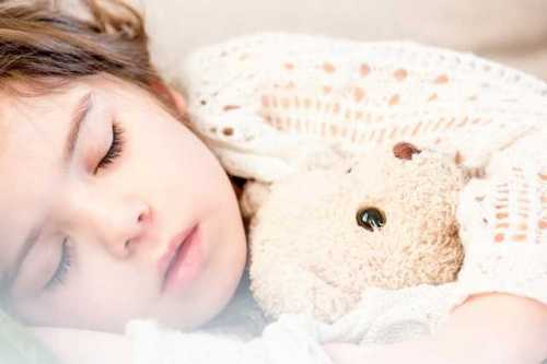 girl sleeping with teddy bear in arms