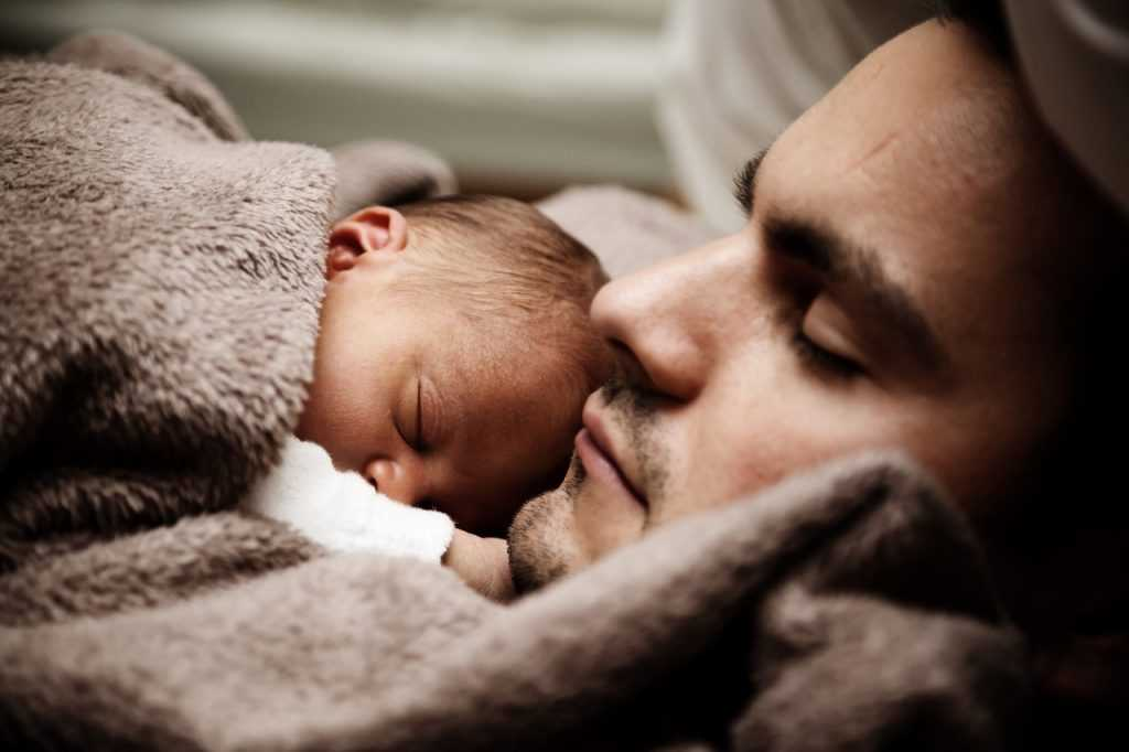 man cuddling baby on his chest with eyes closed