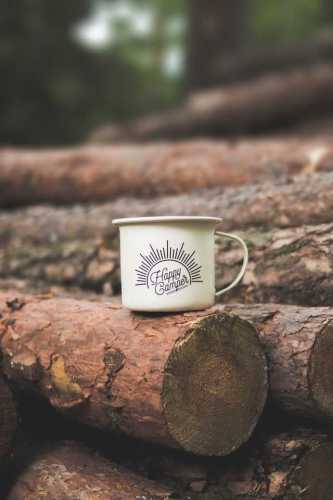 coffee cup sitting on a log