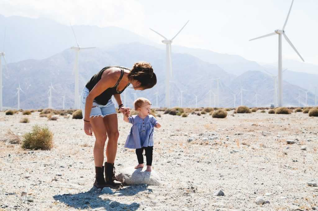 woman standing next to child in front of wind energy turbine