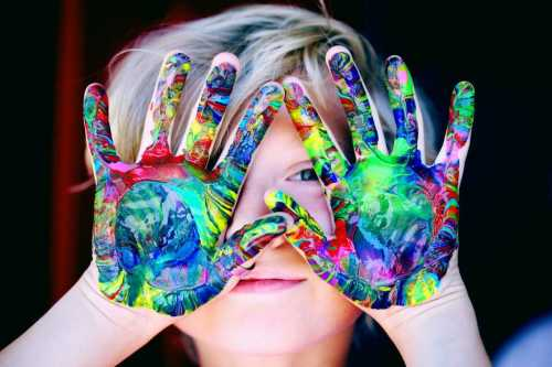 boy holding up paint covered hands in front of his face