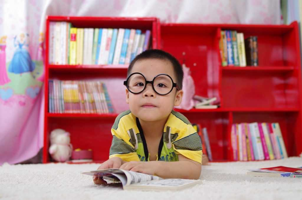 child wearing glasses sitting in front of a red bookcase