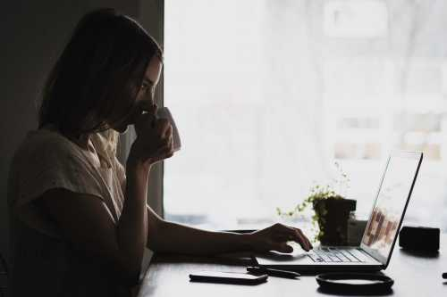woman sitting at a laptop drinking coffee in front of a window