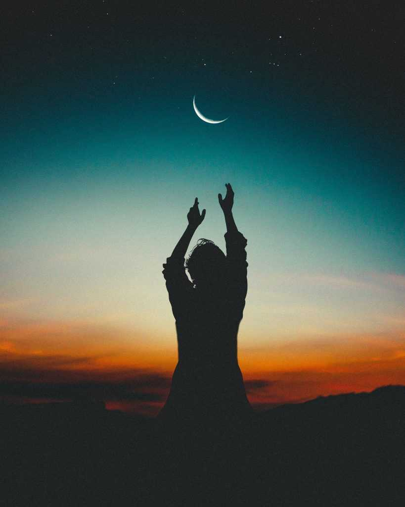 woman reaching her hands up toward the moon at sunset