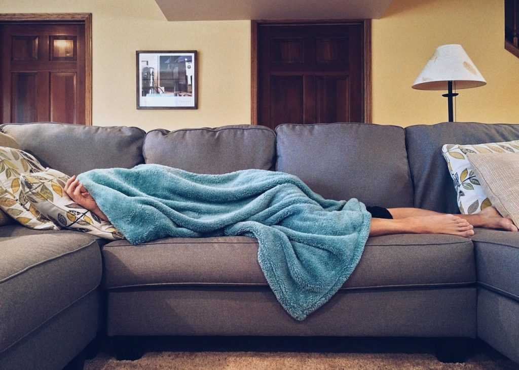 woman lying on a couch under a blanket