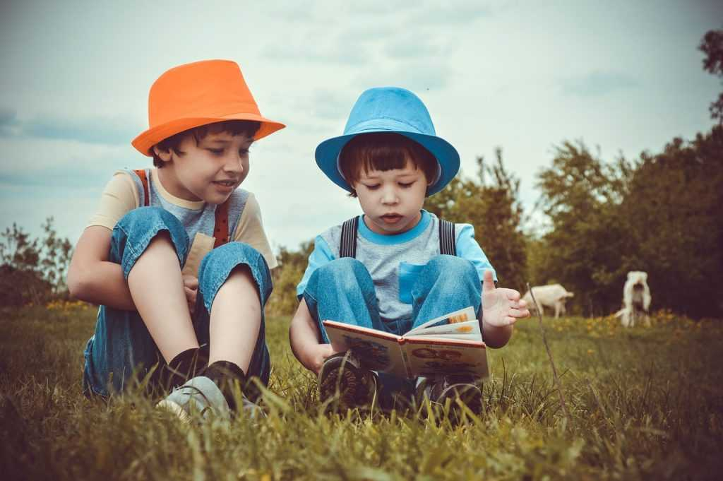 two boys sitting in the grass reading a book together