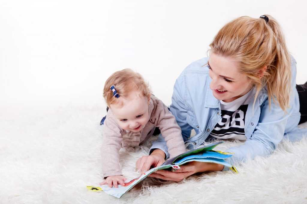 mother reading a book to a child lying on the floor