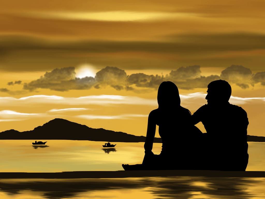 man and woman watching boats on a body of water