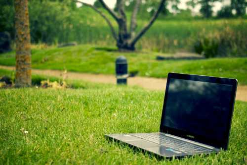 laptop sitting on the grass of a green park