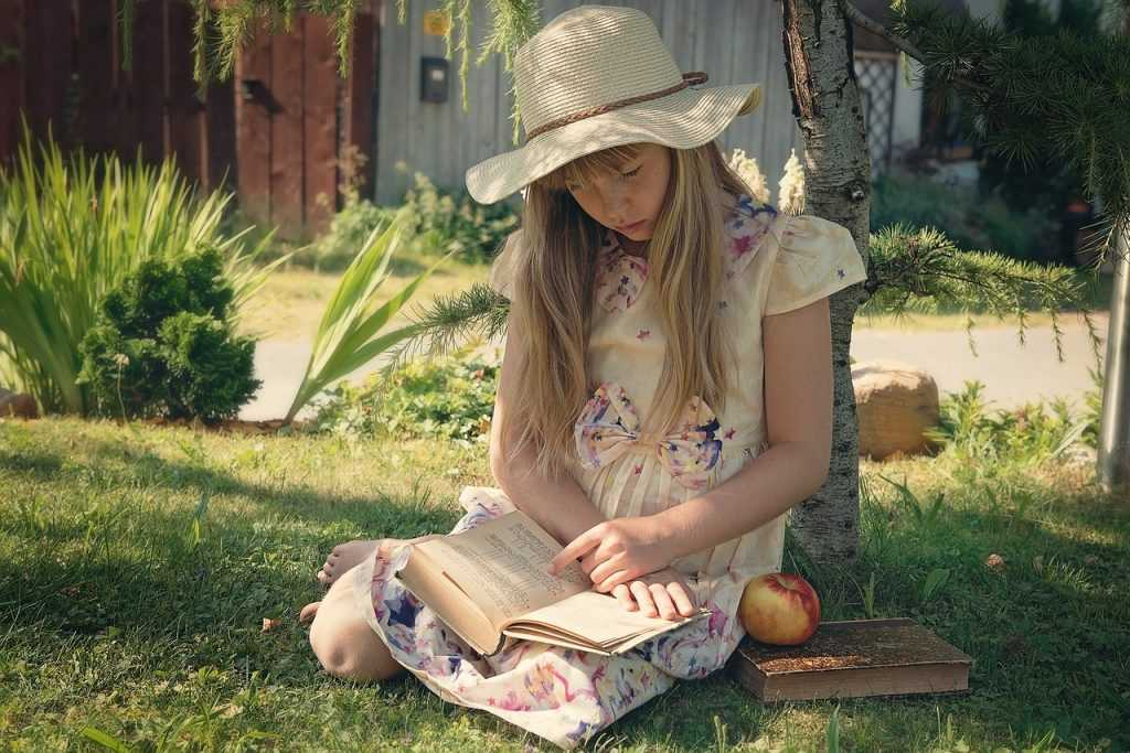 girl sitting in the grass wearing a dress and hat, reading a book
