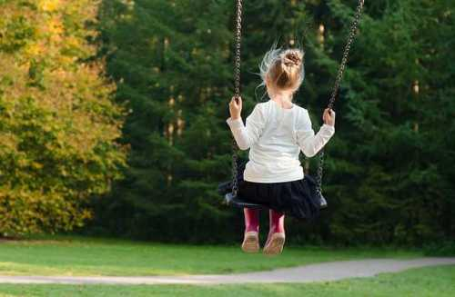 girl swinging on swing in green yard