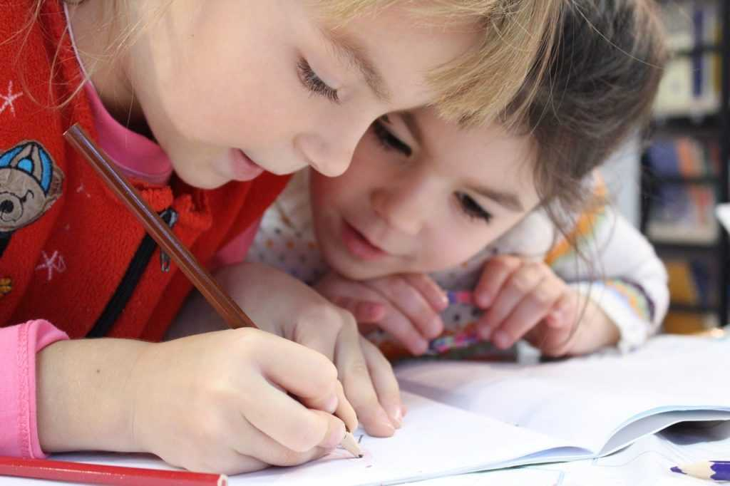 a child writing with another child watching
