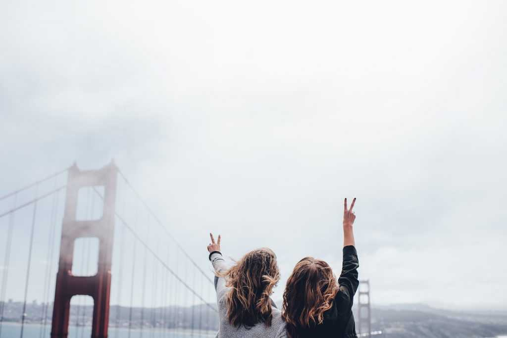 two women giving the peace sign facing the Golden Gate bridge in San Francisco