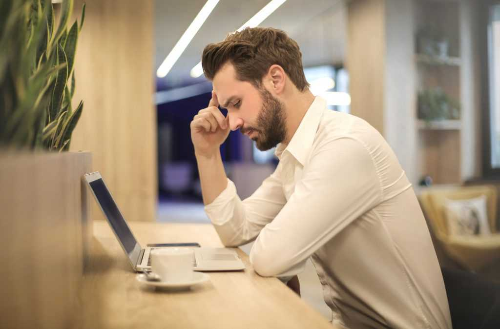 man looking at laptop sitting at a desk