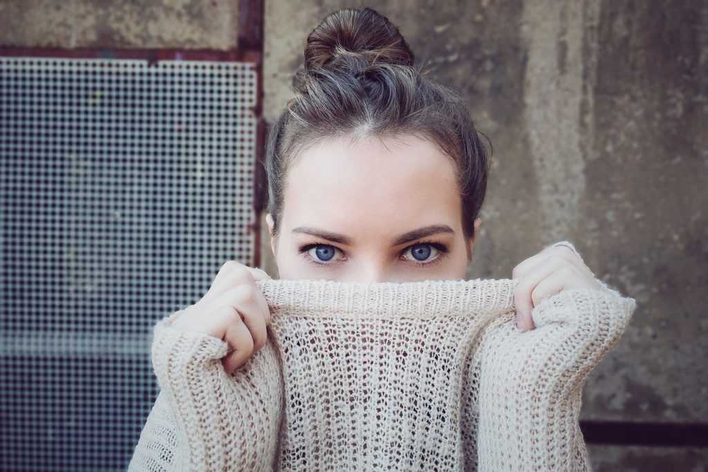 woman looking into the camera, covering up the bottom of her face with a sweater