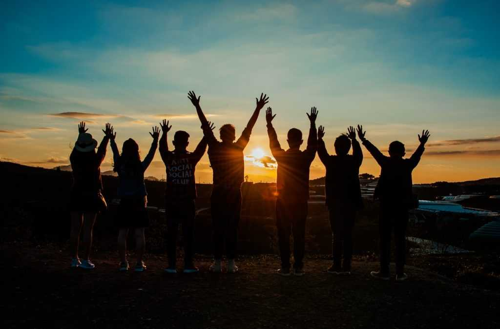 group of people facing a sunset