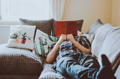 man lying on a couch reading a book