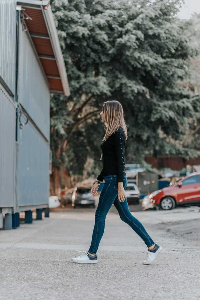 woman wearing jeans walking across the street