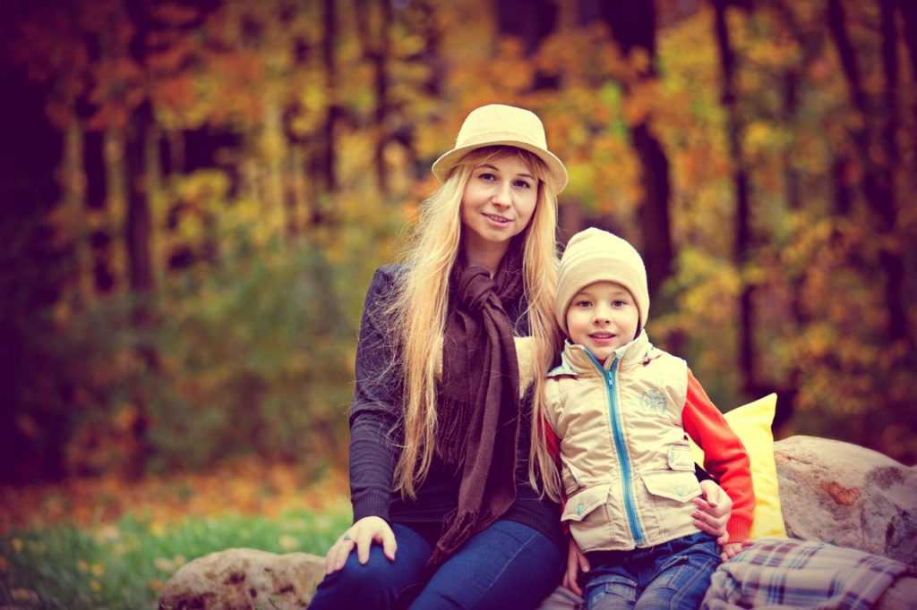 woman and boy sitting down looking into the camera in front of the forest