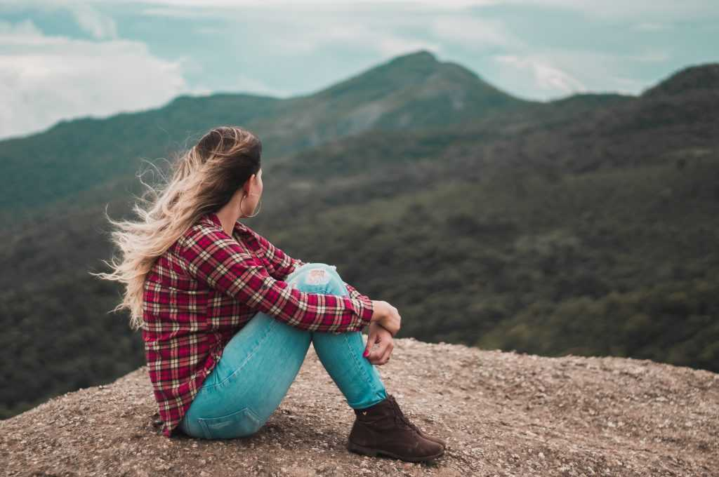 woman sitting with arms around her knees looking at mountains