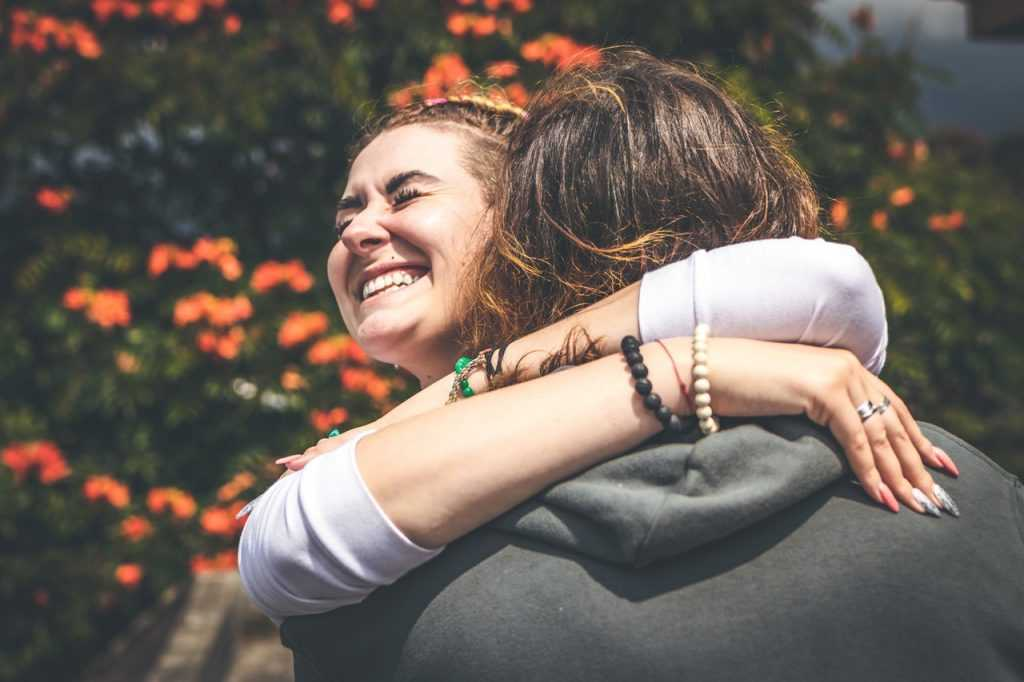 woman hugging another person smiling