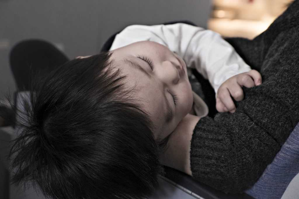 child sleeping in parent's arms