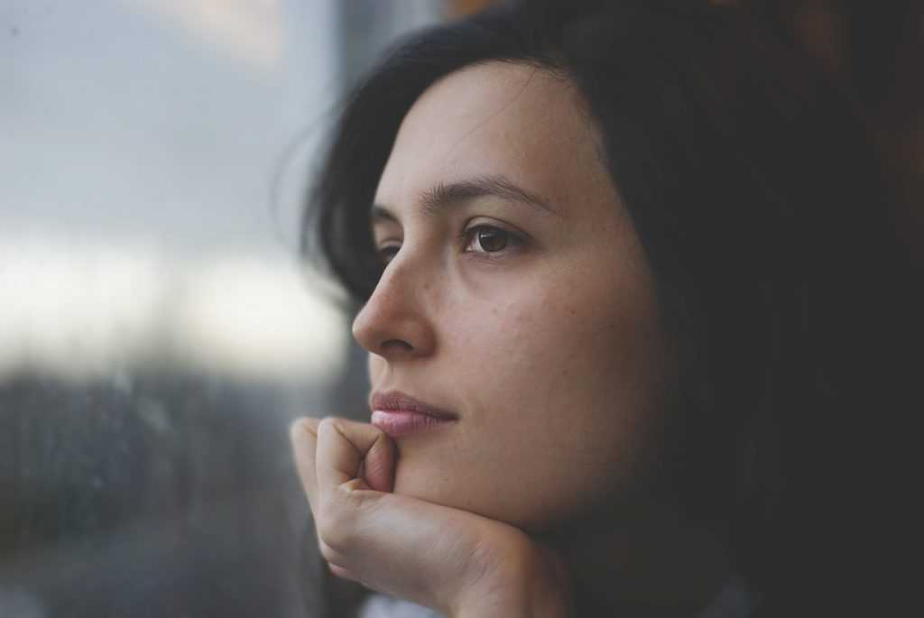 woman looking at window with hand on chin