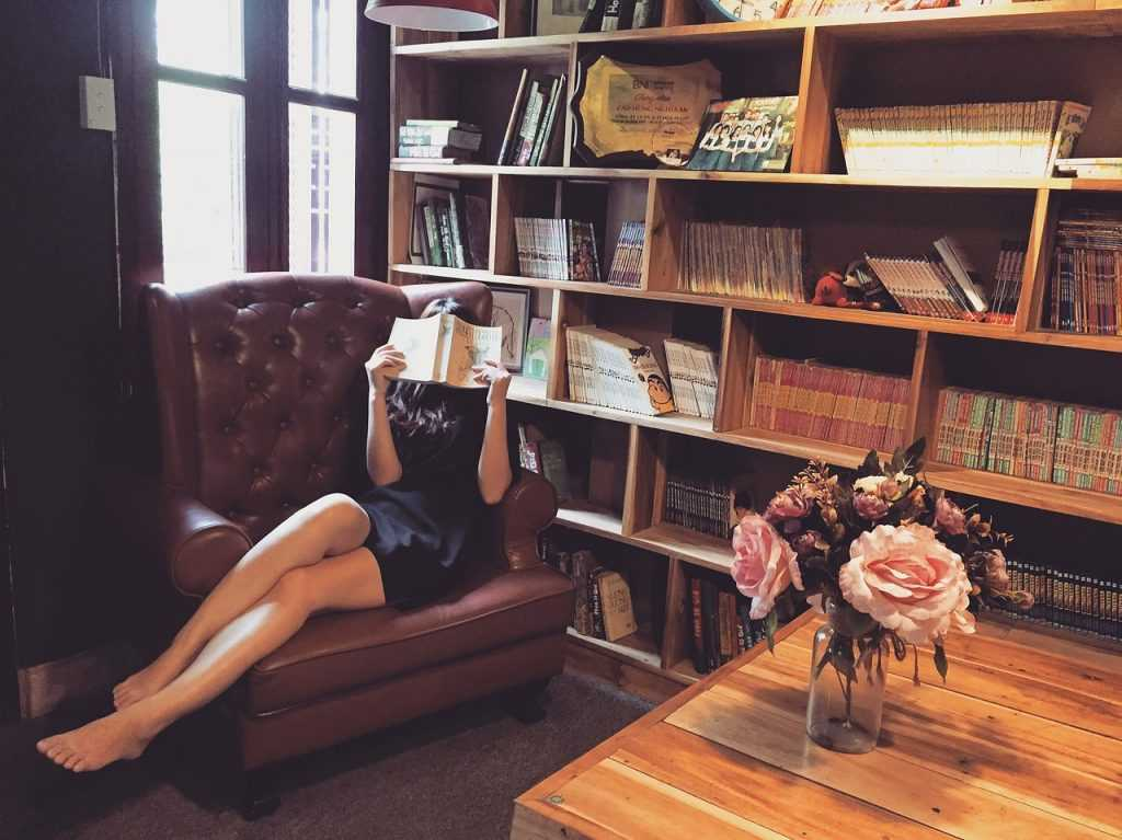 woman sitting in a leather chair reading a book with bookcases full of books behind her
