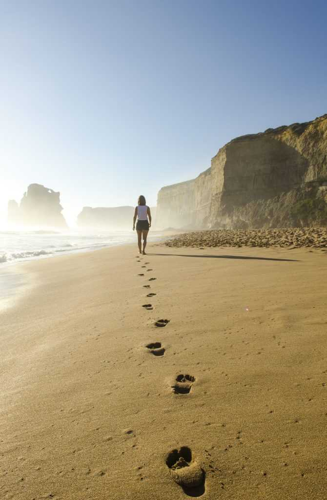 woman walking on the beach, leaving footprints in the sand