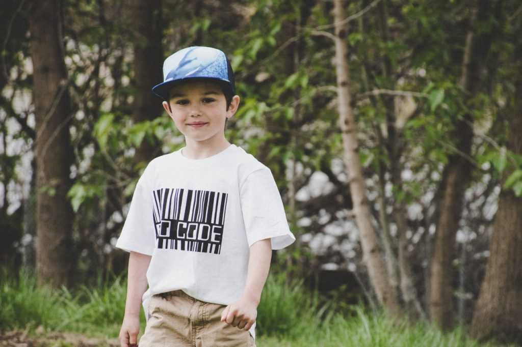 boy standing in a field wearing a shirt and cap