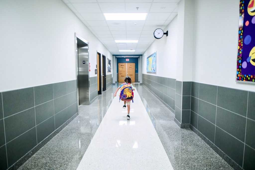 boy walking away down school hallway