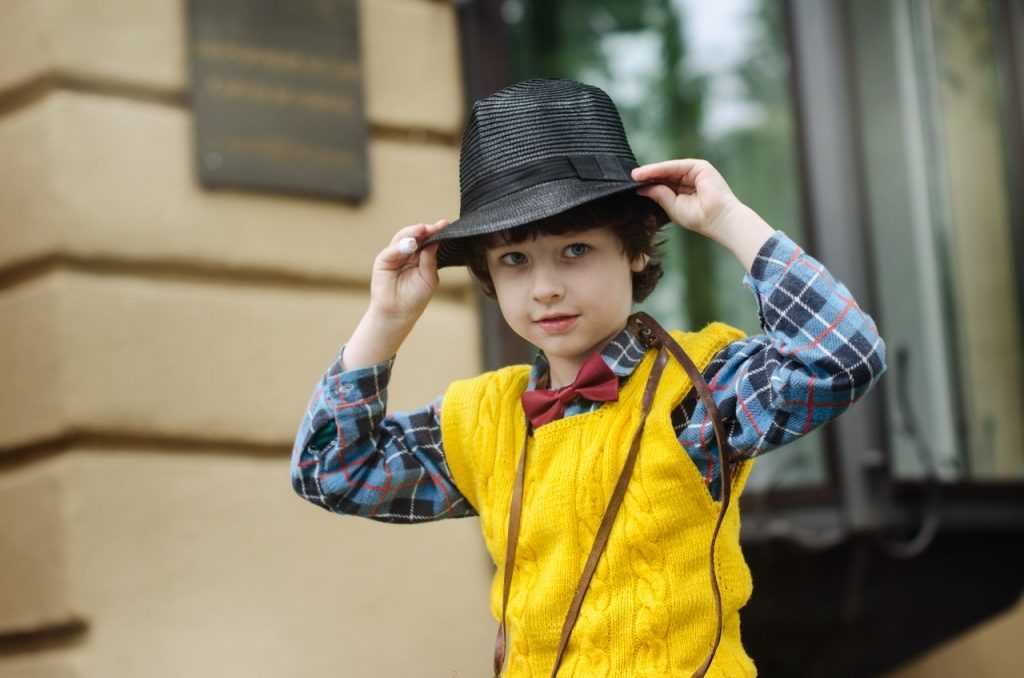 boy wearing yellow vest putting black hat on his head
