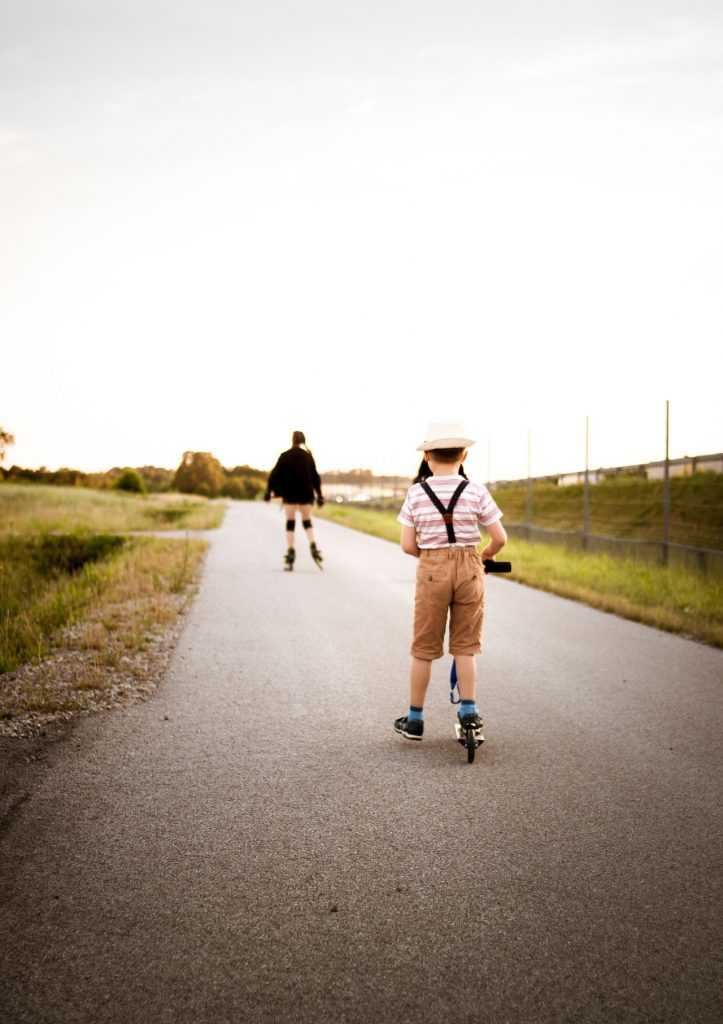 two boys roller skating and scooting on a path