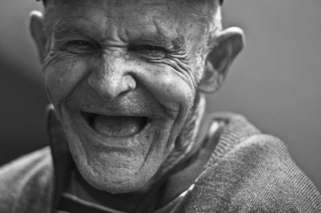 old man laughing, black and white image, toothless and wrinkled