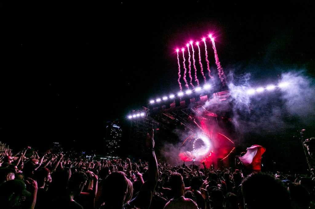 crowd in front of a stage, with fireworks shooting off into the sky