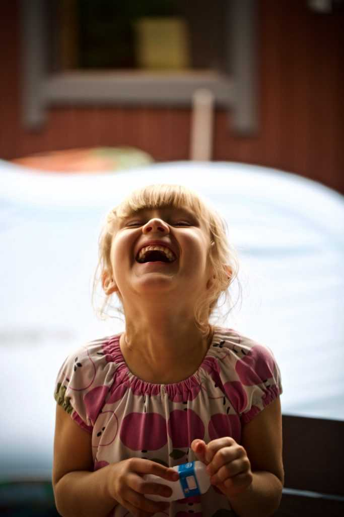 headshot of a child laughing
