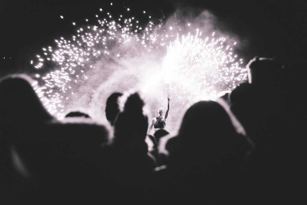 performer on stage, surrounded by fireworks exploding