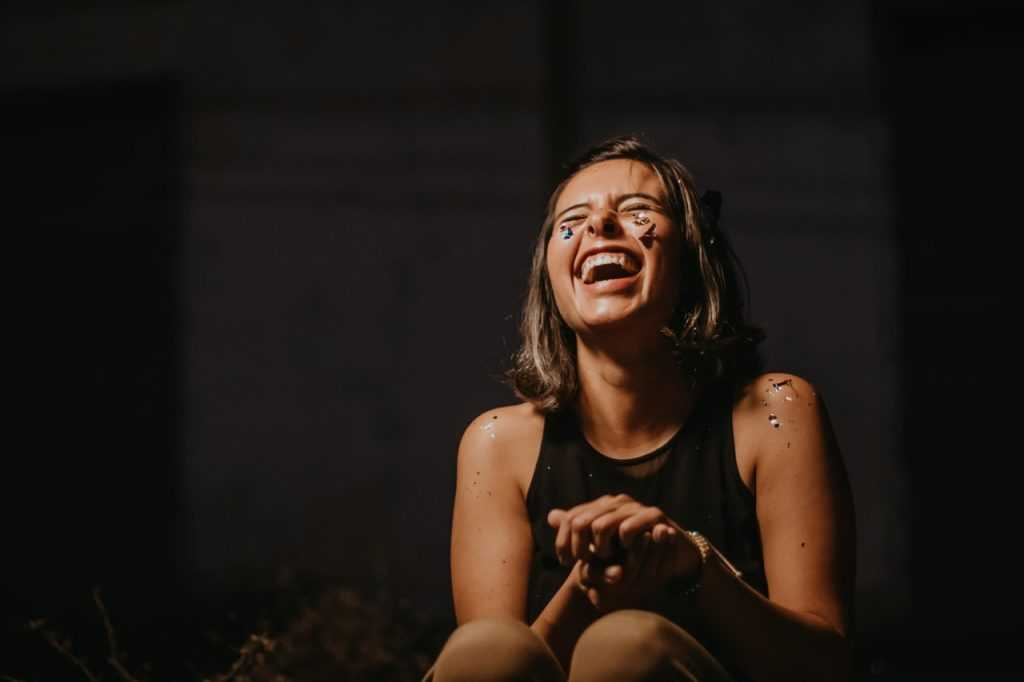 woman laughing, sitting in a crouch with a black background behind her