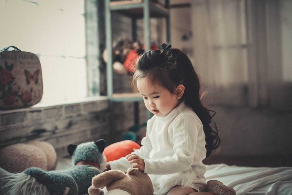 toddler playing with toys in a playroom