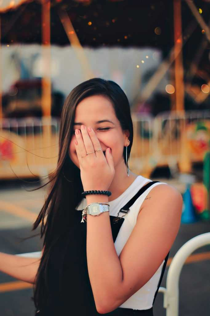 woman laughing with hand over her face, with a carnival in the background