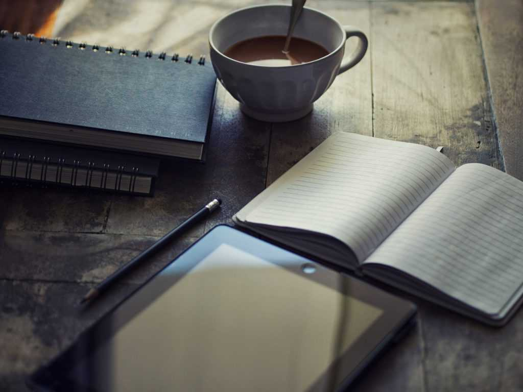 desk with a cup of coffee, tablet and open book