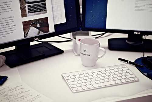 computer on a desk with a coffee cup