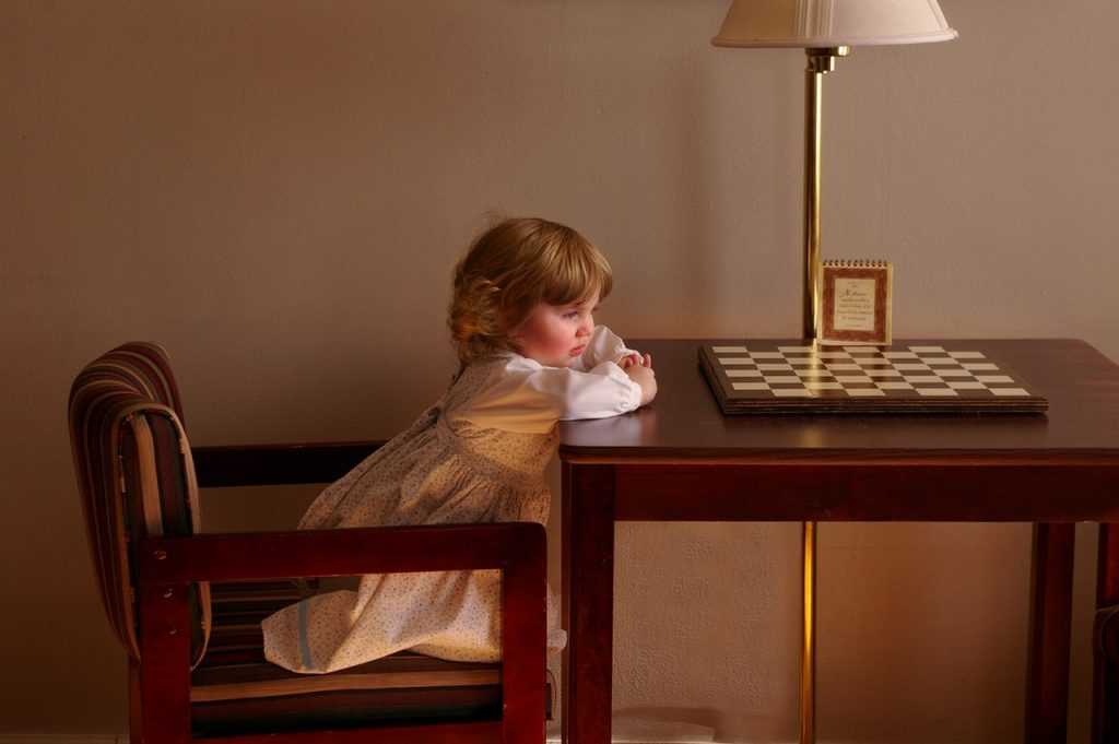 child sitting at a table with empty chessboard