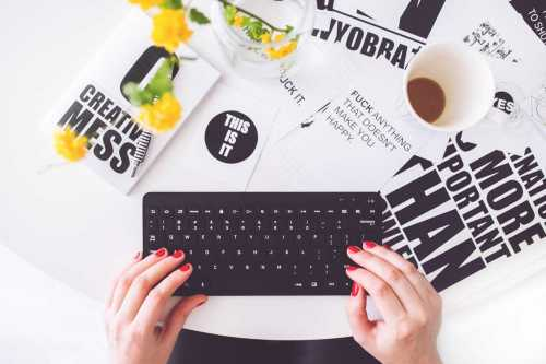 woman using a keyboard with pamphlets on her desk